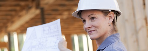 woman in hard hat holding a blueprint at a construction site