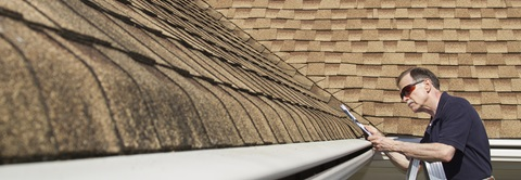 Man inspecting roof shingles