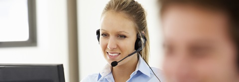 woman with telephone headset in front of computer